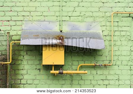 Old yellow pipeline and box covered with corroded tin sheet on green brick wall horizontal