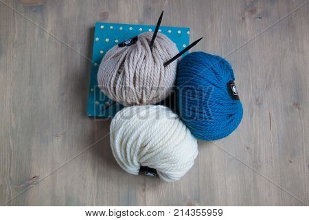 Yarn balls with knitting needles and a nice frame on the wooden background. Toned.