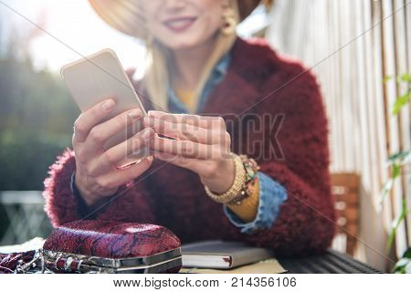 Low angle close up of arms of young joyful woman using cellphone for communication. She is relaxing at table outdoor. Focus on mobile phone