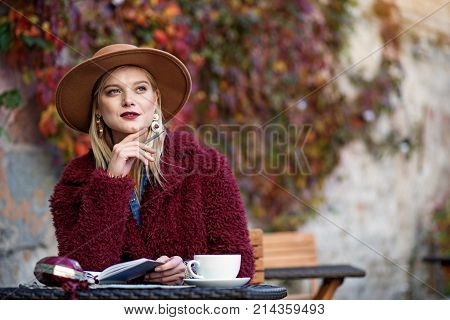 Inspired by autumn nature. Waist up portrait of dreamful young woman writing poem while sitting in cozy cafe outdoor. Copy space