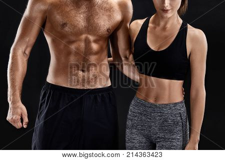 Sport, fitness, workout concept. Fit couple, strong muscular man and slim woman posing on a black background. A man in shorts and a naked torso and a woman in sportswear