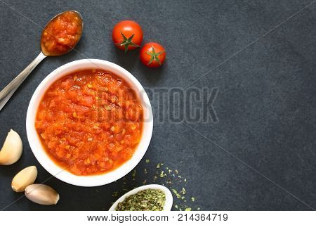 Homemade traditional Italian marinara or pomodoro tomato sauce made of fresh tomato garlic dried oregano and salt served in bowl with ingredients on the side photographed overhead on slate with natural light (Selective Focus Focus on the top of the sauce)