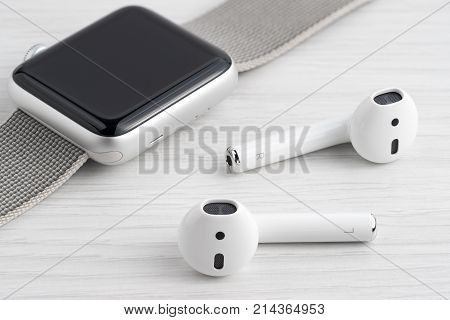 UFA RUSSIA - OCTOBER 20 2017: AirPods wireless headphones developed by Apple Inc. AirPods are on the table and apple watch.