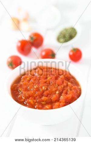 Homemade traditional Italian marinara or pomodoro tomato sauce made of fresh tomato garlic dried oregano and salt served in bowl with ingredients in the back photographed on white wood with natural light (Selective Focus Focus in the middle of the sauce)