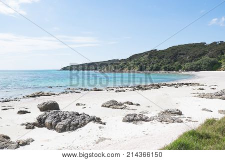 Beautiful empty beach on Karikari Peninsula Far North Northland New Zealand NZ in summer - clear blue water white sand and rocks