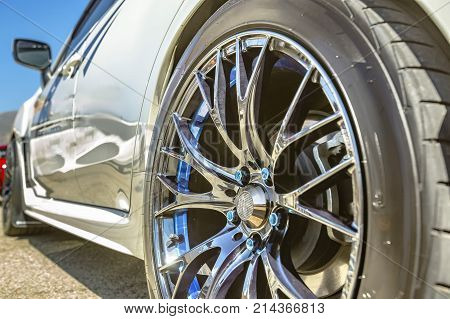 Close Up Of A Car's Rim, Wheel With No Emblem Chrome Rims And Blue Bolts On A White Car
