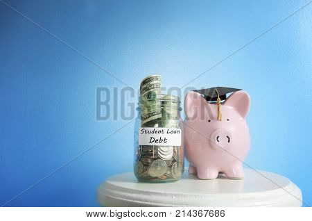 Piggy bank with graduation cap beside a student loan coin jar