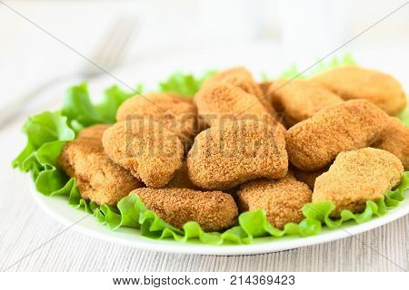 Fried breaded crispy chicken nuggets on lettuce leaves on plate photographed with natural light (Selective Focus Focus one third into the chicken nuggets)