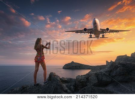 Beautiful woman makes photo of landing aircraft at sunset. Summer landscape with girl standing on the rocks and flying passenger airplane against colorful sky. Woman and landing commercial plane.