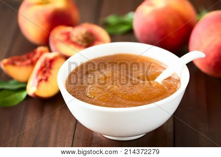 Peach jam or jelly in bowl with fresh ripe peach fruits in the back photographed on dark wood with natural light (Selective Focus Focus one third into the jam)