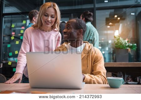 Let me see. Low angle of african man is sitting at table with laptop while gazing at young woman with smile. She is standing behind him and looking at screen while enjoying their cooperative work