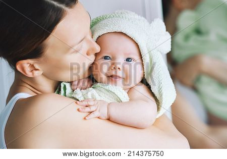 Mom hugs her little cutest baby after bath with towel on head. Child caring routine. Family life. Mother and baby.
