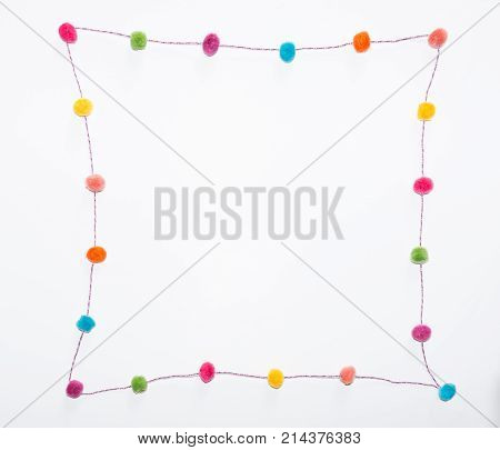 Colorful pom poms in fuchsia orange yellow coral turquoise green and purple arranged in a curvilinear square against a white background.