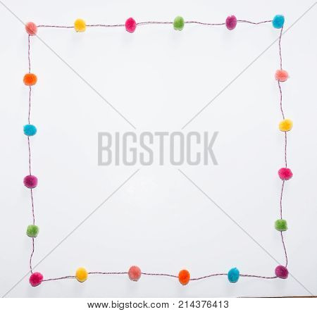 Colorful pom poms in fuchsia orange yellow coral turquoise green and purple arranged in a square against a white background.