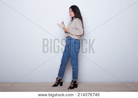 Beautiful Asian girl writing a poem in her notebook and smile. Do homework isolated on white background. Brain girl do her lessons. University exams