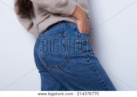 Sexy body of a beautiful girl. Attractive butt in blue jeans. Close up of sexy butt isolated on white background