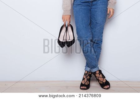 Choice which high heel shoes wear today. Fashion jeans on a girl, girl holding a pair of shoes. Thin legs of fashion girl. Shapely female legs in high heel shoes and jeans near a white wall