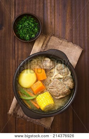 Traditional Chilean Cazuela de Vacuno or Cazuela de Carne a beef soup with potato corn pumpkin carrot bell pepper onion and rice cut parsley on the side photographed overhead on dark wood with natural light (Selective Focus Focus on the soup)