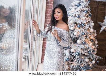 Christmas party. Beautiful dressed and sexy young Asian girl waiting for her friends while standing near windows and looking at the camera with glass of champagne