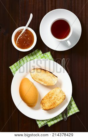 Toasted bread rolls with peach jam in bowl and tea on the side photographed overhead on dark wood with natural light