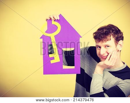 Dream about stabilization and family. Young man with paper house and big key. Dreaming boy full of plans ideas. New flat apartment.