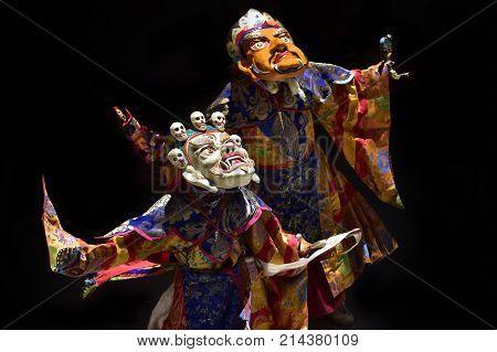 Buddhist lamas perform the Dance of Zam: two monks in the Tibetan sacral masks of White Mahakala and the Yellow Mask of Shambhala Himalayas Tibet.