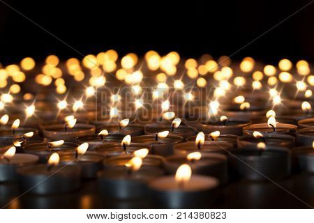 Tealight candles. Beautiful Christmas celebration religious or remembrance candlelight image. Romantic candlelit vigil. Selective focus against black background.