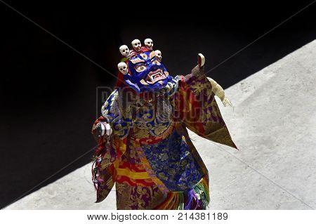 Buddhist lama wearing the mask Blue Mahakala and ritual clothing performs the Dance of Tsam in the monastery of Karcha Zanskar Northern India.
