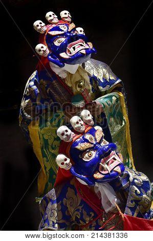 Dance of Tibetan lamas in masks of Blue Mahakala and festive robes Buddhist mystery sacred ritual of ancient Tibet.
