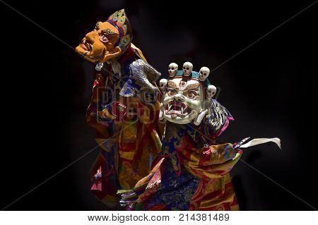 Two lamas perform the Mask Dance: in the foreground Lama in the white mask of Mahakala in the background a lama in the yellow mask of Shambhala.
