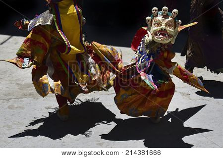Two Buddhist lamas in ritual bright outfits and sacral masks with skulls perform a dynamic dance in the courtyard of the monastery of Karcha Zanskar Northern India.