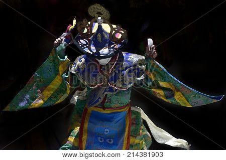 Religious dance tibetan monk in ethnic dress with ritual objects in his hands ancient Tibetan ritual the Himalayas Northern India.