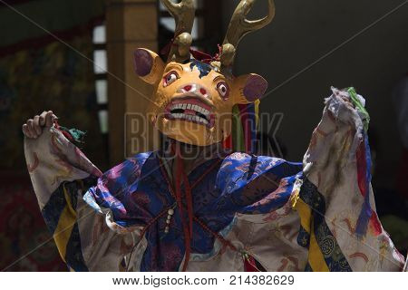 Tibetan monk in the Tantric Deer Mask and ritual attire against the wall of the monastery Tibet.