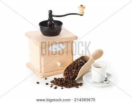 Coffee grinder with coffee beans in wooden scoop and cup of espresso on white background