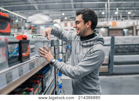 male customer buying car battery n the car supermarket. Difficult decision which battery to buy. He looks happy