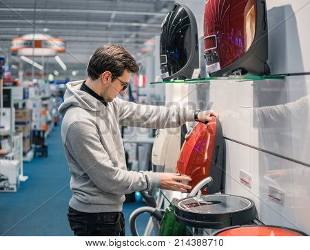 Smart customer buying new vacuum cleaner. Purchasing new home appliances. Modern electronics upgrade. Choice between robot vacuum cleaner and old one.