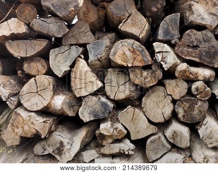 Wall of wooden chocks firewood stacked together old chopped brown and beige trunks color.