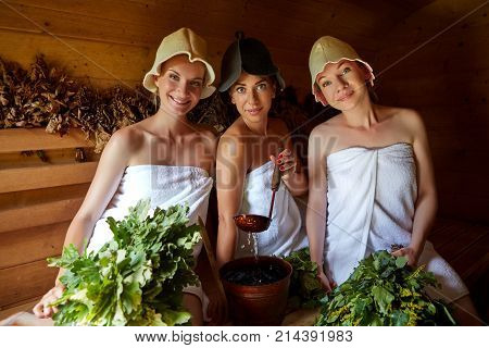 three beautiful young women in towels realxing in wooden sauna. inside shot with natural light. poster