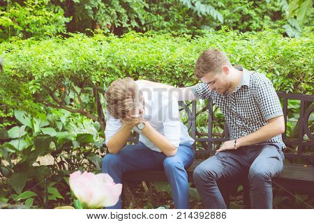 American Businessmen Consoling Friend. Frustrated Young Man Being Consoled By His Friend In Garden.