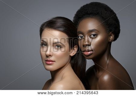 Beautiful young black woman with natural make up and glowing skin in white veil fashion hat. Beauty shot on grey background. Copy space.