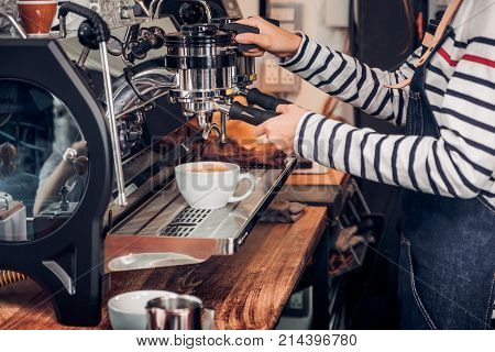 Close up woman barista making hot coffee with machine at counter bar in cafe restaurantFood and drink service concept.
