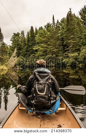 Girl canoeing with Canoe on the lake of two rivers in the algonquin national park in ontario Canada on a cloudy day