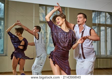 beautiful young couple dancing bachata in dance studio mirror room. woman in purple dress and man in white suit. copy space.