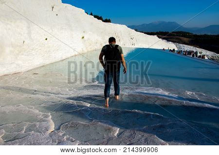 torist walking in the slippery water pool warming his feet in thermal water