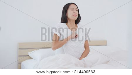Woman feeling pain and tired on bed