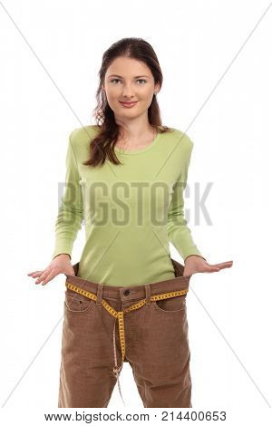 Teenager girl wearing several sizes too big trousers, holding it up with hand, using measuring tape as belt, looking at camera, smiling. Isolated on white.