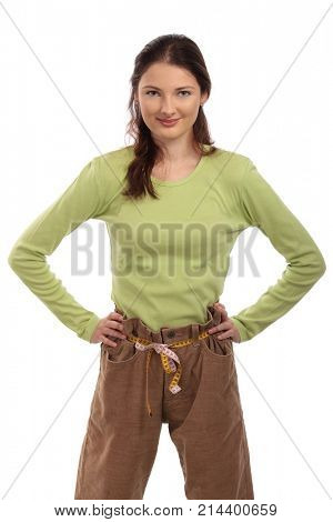 Teenager girl wearing several sizes too big trousers, constricting it with measuring tape as belt. Cut out, isolated on white.