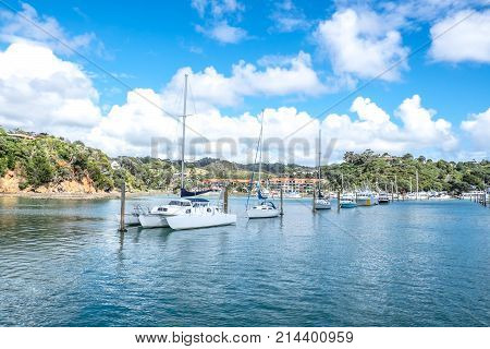 Sail boats and motor launches berthed at pile moorings in entrance to Tutukaka Marina Northland New Zeealand NZ - copy space in sea