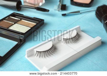 Makeup set with false eyelashes on color background