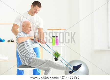 Elderly patient training with rubber band under doctor's supervision in physiotherapy center